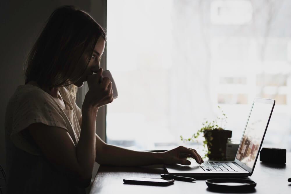 Eine Frau im Profil, sie sitzt vor ihrem Laptop und trinkt dabei aus ihrer Tasse