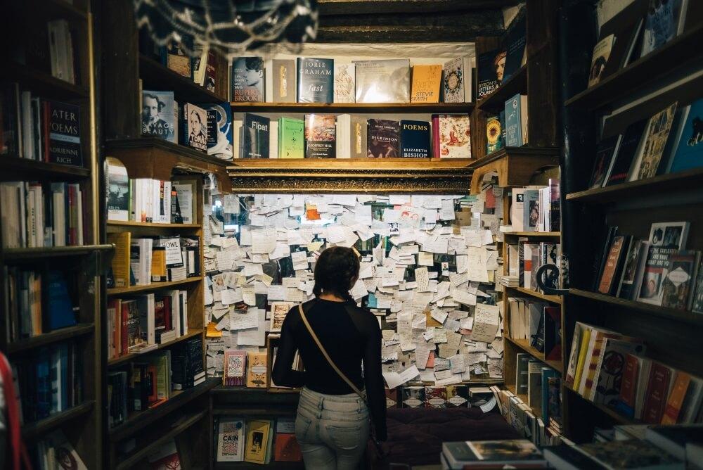Storyboard - Eine Frau steht vor einer Pinnwand, die übersät ist mit kleinen Zetteln