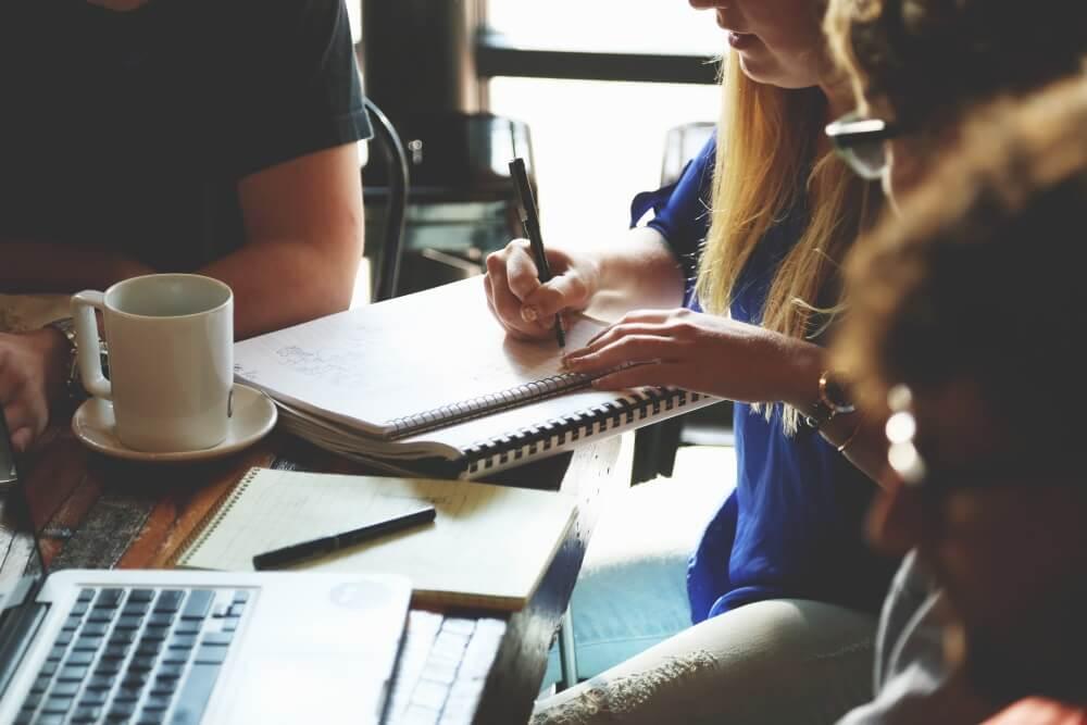 Creative Writing Kurs - Eine Gruppe junger Menschen sitzt um einen Tisch, eine Frau schreibt in ihr Notizblock