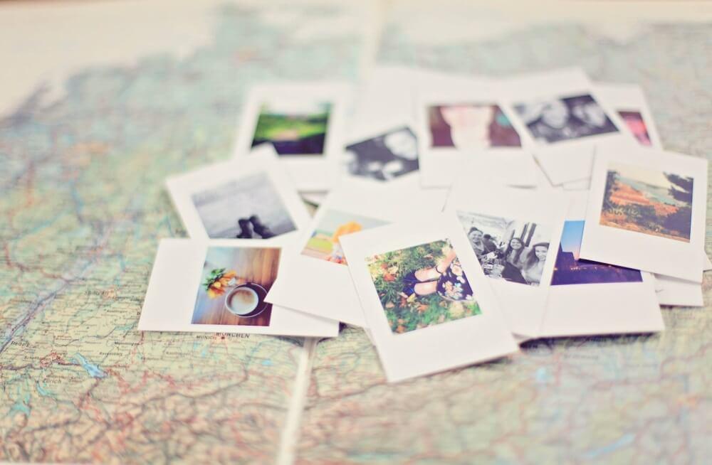 Schreiben auf Reisen - Polaroid-Bilder liegen verteilt auf einer Landkarte
