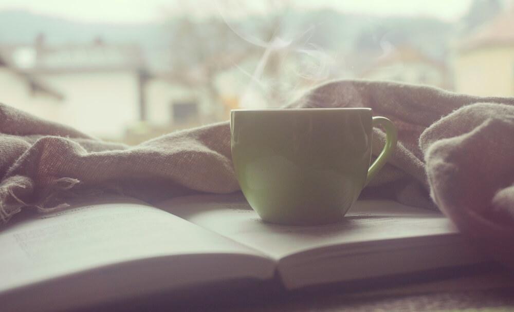 Ein aufgeschlagenes Buch auf einer Fensterbank, darauf steht eine dampfende Tasse Tee