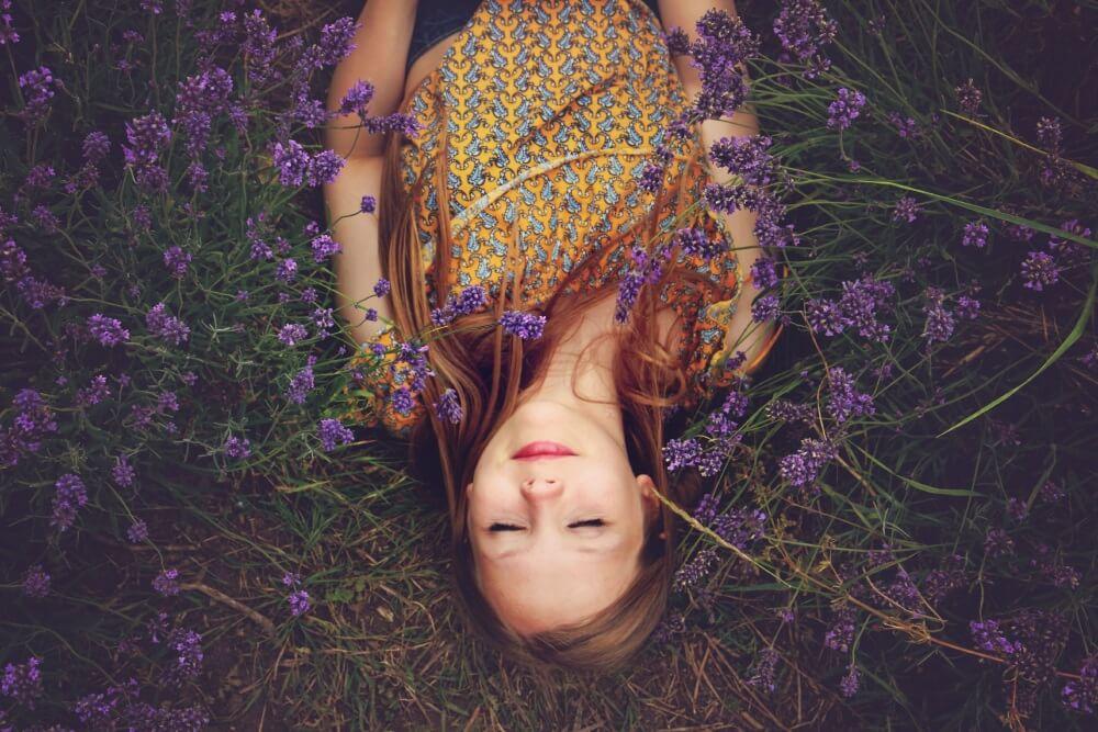 Eine junge Frau liegt mit geschlossenen Augen in einer Wiese