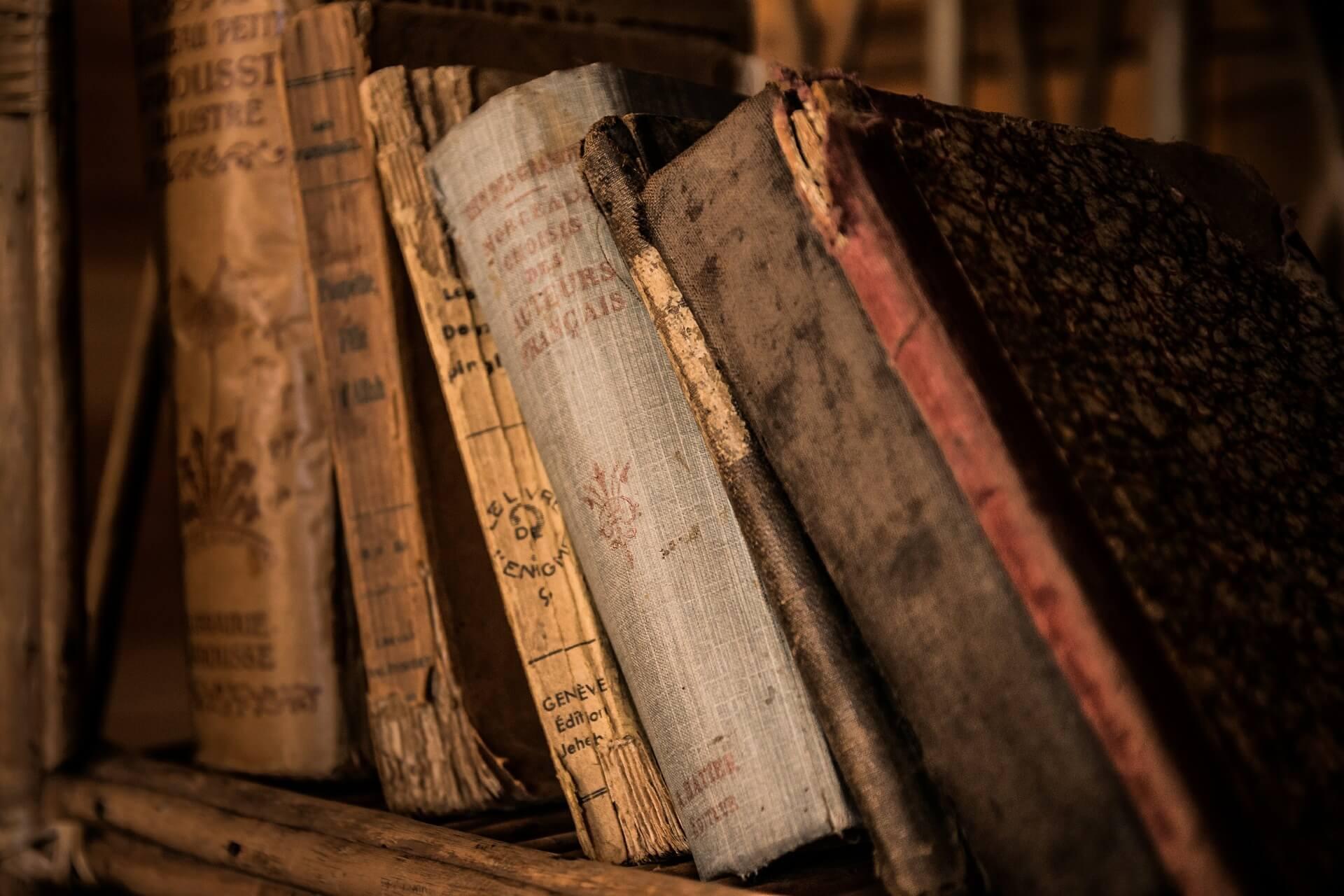 Alte Bücher lehnen in einem Bücherregal schräg übereinander