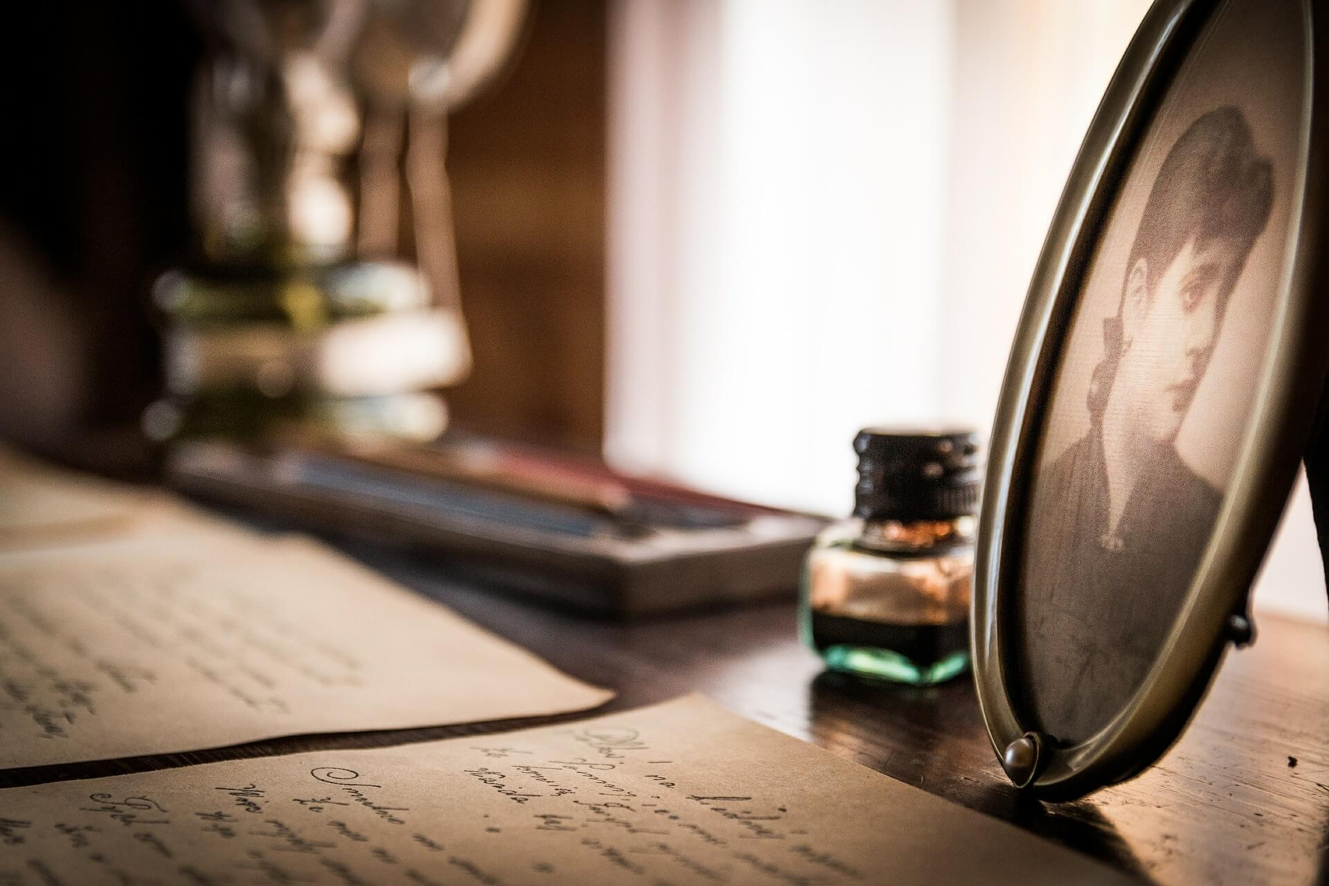Handgeschriebene Briefe liegen auf einem Schreibtisch, daneben ein ovaler Bilderrahmen mit dem Bild einer Frau