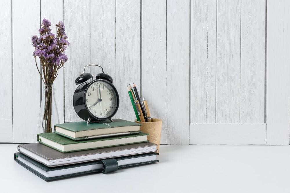 Ein Wecker steht auf einem Stapel Bücher