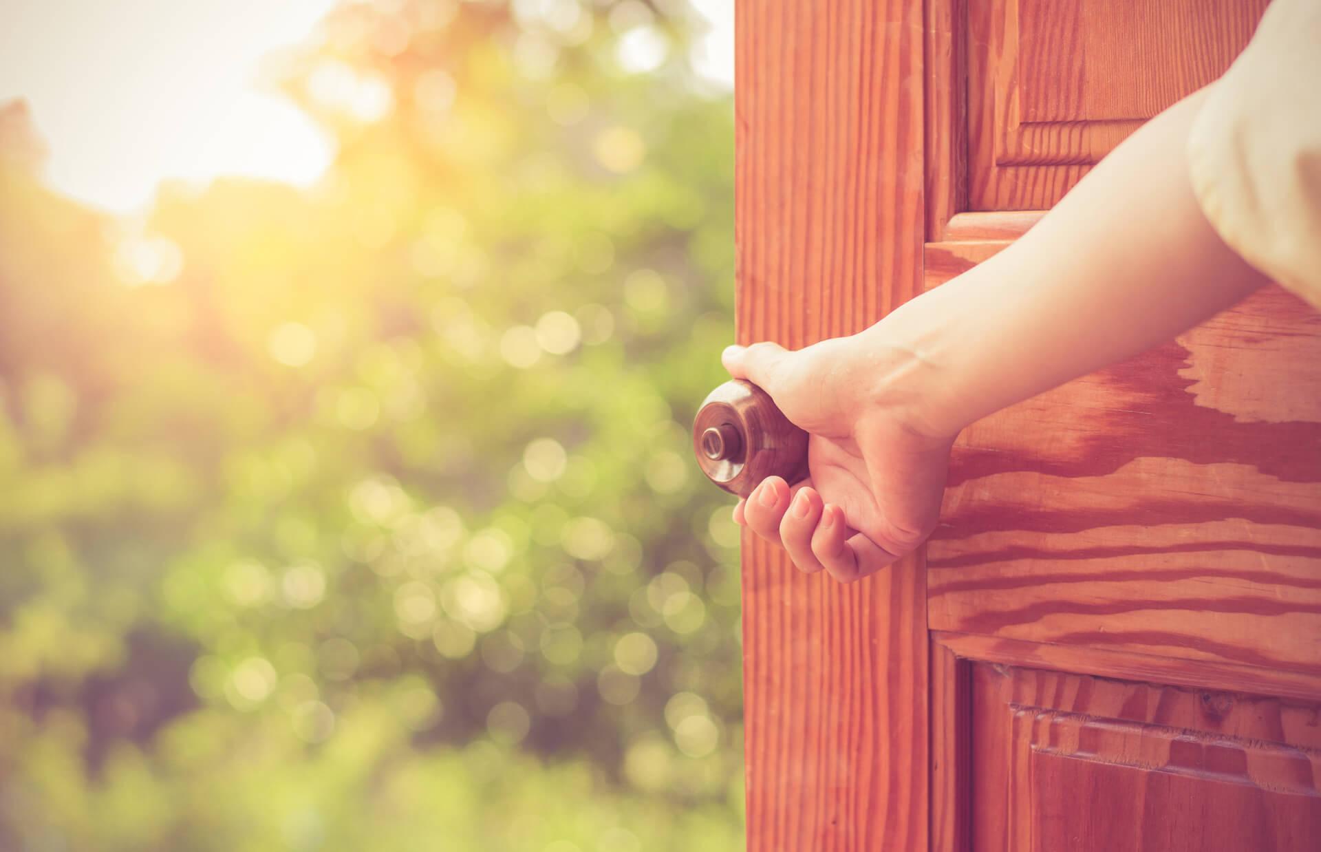Den Anfang schreiben: Frauenhand öffnet eine Tür, hinter der sich ein Garten zeigt