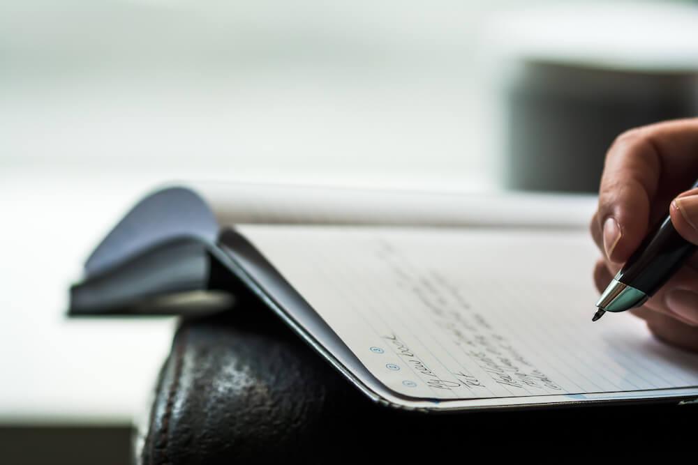 Männerhand schreibt in ein Notizbuch
