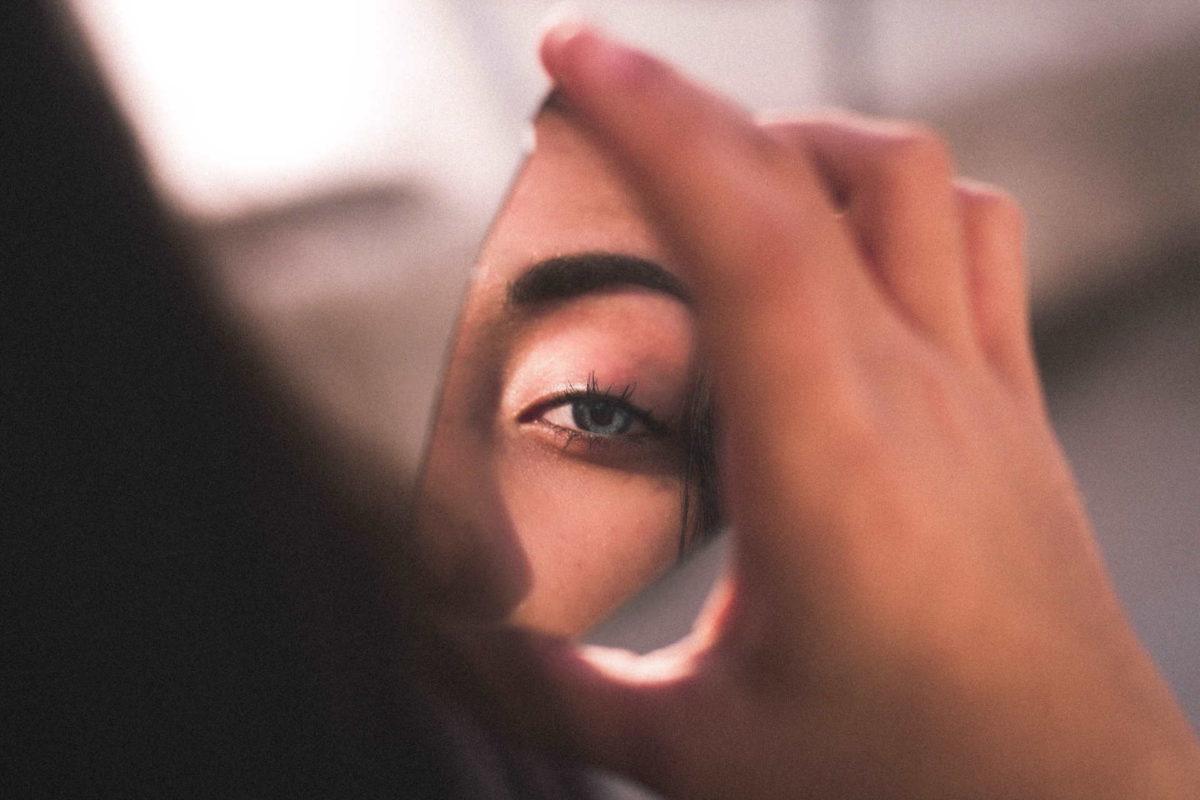 Frau betrachtet ihr Gesicht in einer Spiegelscherbe